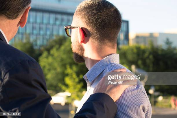 older businessman placing hand on shoulder of younger businessman - hand on shoulder stock pictures, royalty-free photos & images