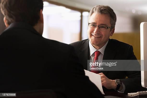 Älterer Geschäftsmann lächelnd im jüngeren Kollegen