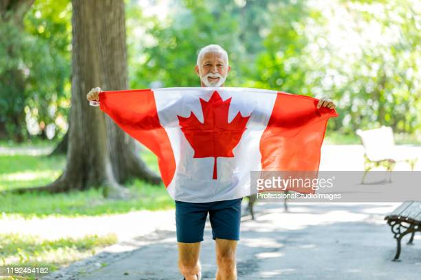 older canadian patriot with the national flag - canadian flag stock pictures, royalty-free photos & images