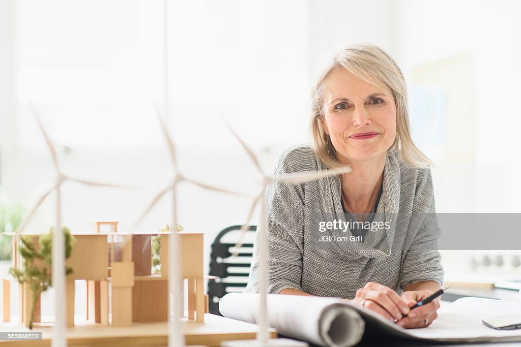 Older Caucasian architect sitting in office : Stock Photo