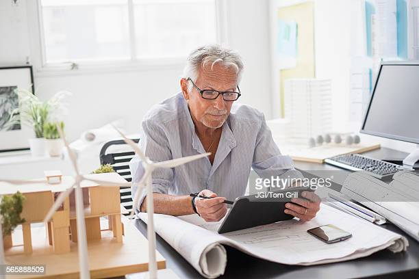 older caucasian architect using digital tablet in office - old windmill stock photos and pictures