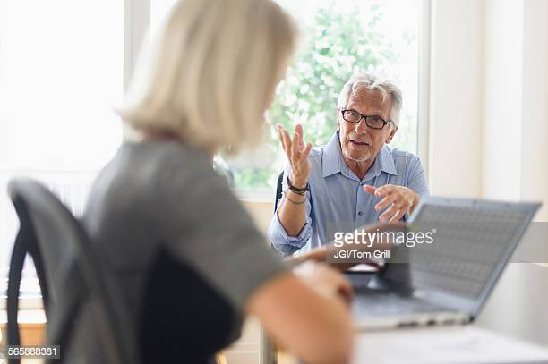 Older Caucasian business people arguing in office meeting