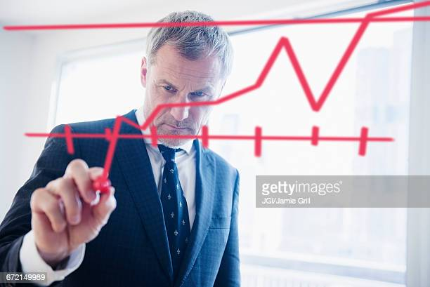 Older Caucasian businessman drawing chart on glass wall