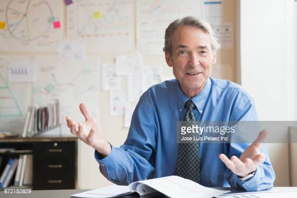 Older Caucasian businessman gesturing in office