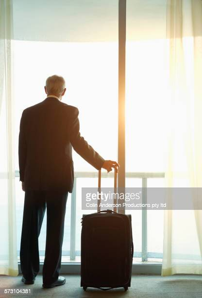 Older Caucasian businessman looking out hotel window