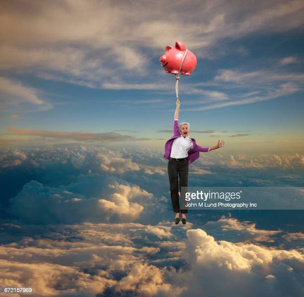Older Caucasian businesswoman floating in sky holding flying piggy bank