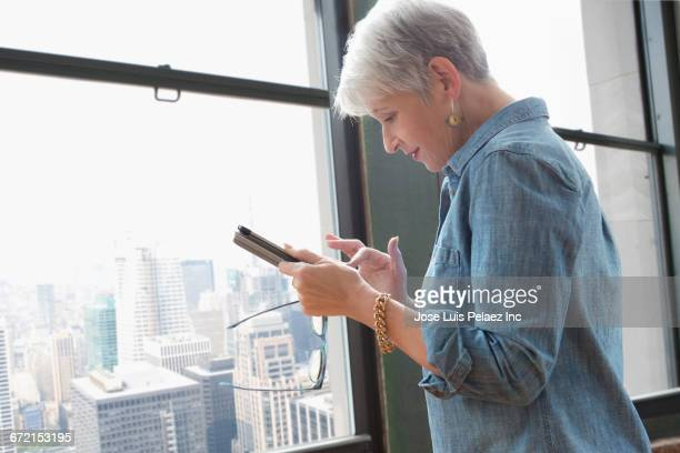 Older Caucasian businesswoman texting on cell phone in office