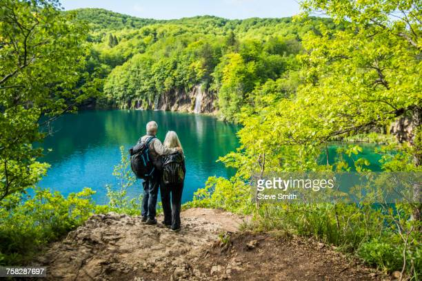 Older Caucasian couple admiring waterfall