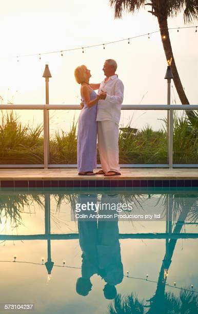 Older Caucasian couple dancing at swimming pool