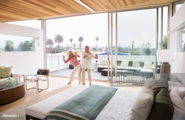 Older Caucasian couple dancing in bedroom