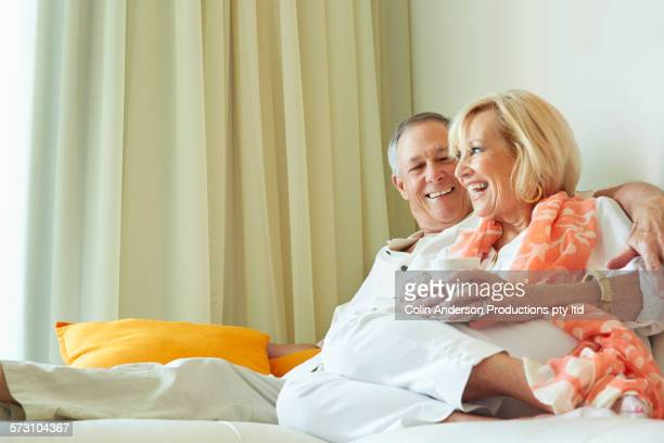 Older Caucasian couple drinking coffee in hotel room