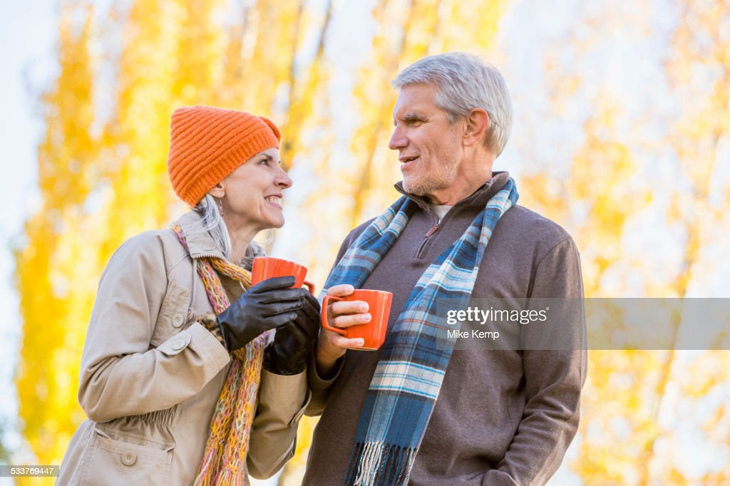 Older Caucasian couple drinking coffee near autumn trees : Foto stock