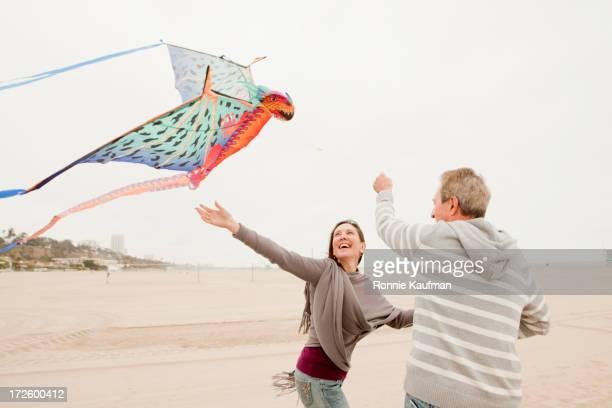 Older Caucasian couple flying kite on beach