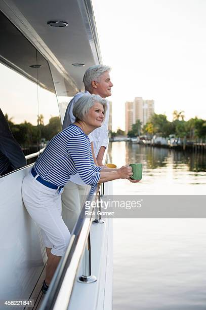 Older Caucasian couple having coffee on boat deck