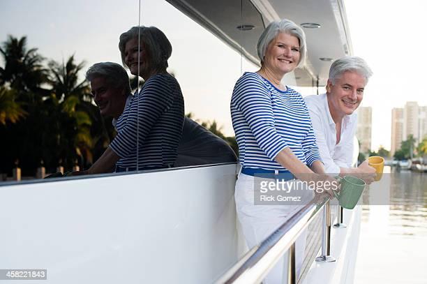 Older Caucasian couple having coffee on boat deck