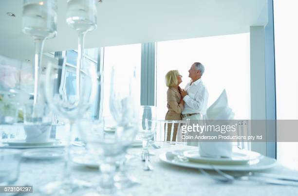 Older Caucasian couple holding hands in dining room