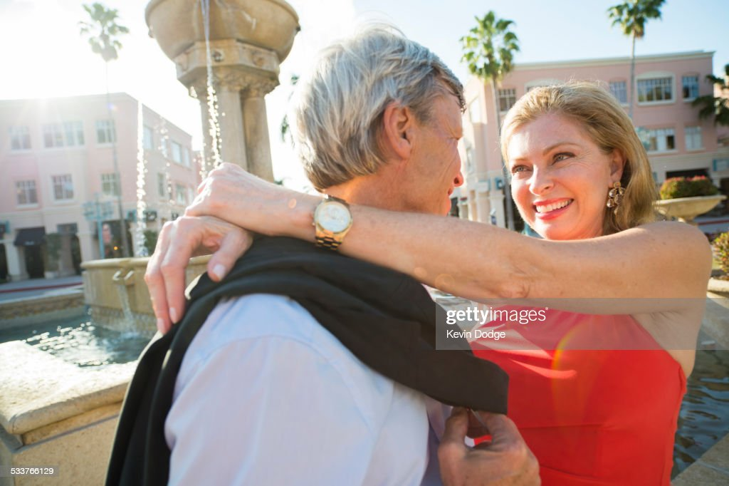 Older Caucasian couple hugging near fountain : Foto stock