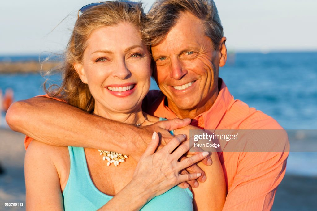 Older Caucasian couple hugging on beach : Foto stock