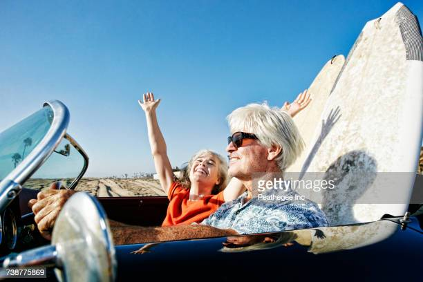 Older Caucasian couple in convertible car with surfboards on beach