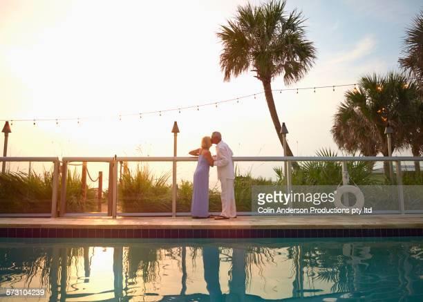 Older Caucasian couple kissing at swimming pool