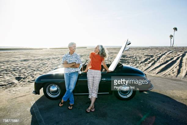 older caucasian couple leaning on convertible car with surfboard on beach - escapism stock pictures, royalty-free photos & images