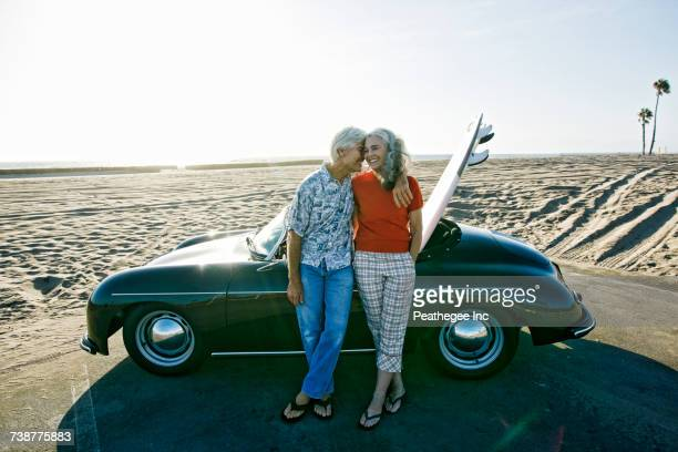 older caucasian couple leaning on convertible car with surfboard on beach - activity stock pictures, royalty-free photos & images