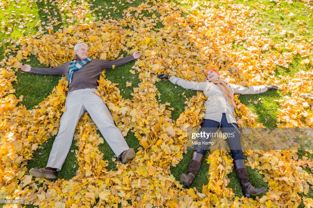 Older Caucasian couple playing in autumn leaves : Foto stock