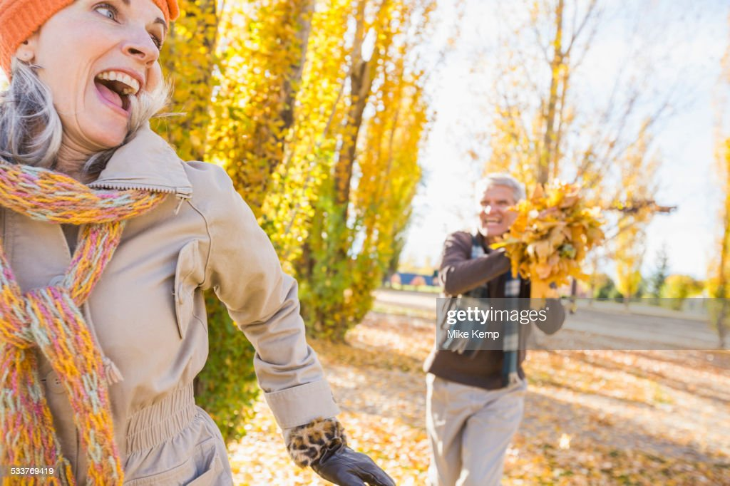 Older Caucasian couple playing with autumn leaves : Foto stock