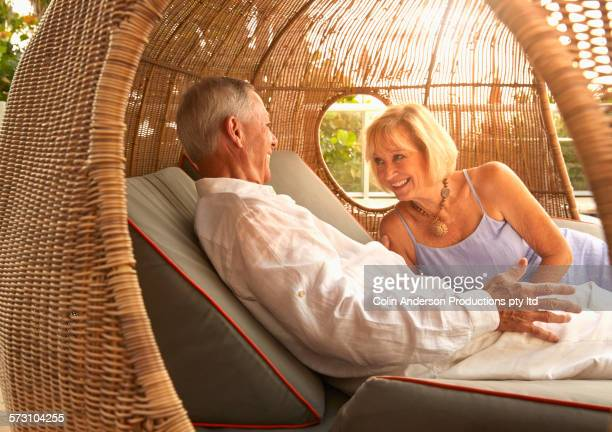 Older Caucasian couple relaxing in cabana