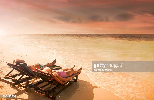 Older Caucasian couple relaxing on beach at sunset