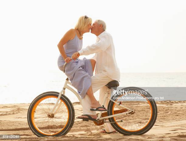 Older Caucasian couple riding bicycle on beach