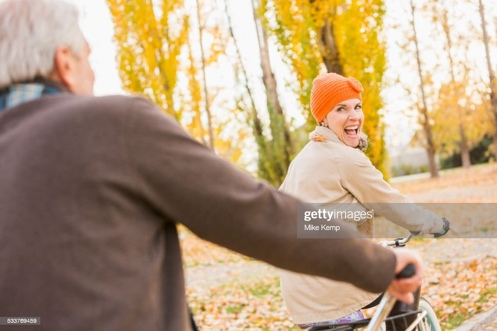 Older Caucasian couple riding bicycles on autumn leaves : Foto stock