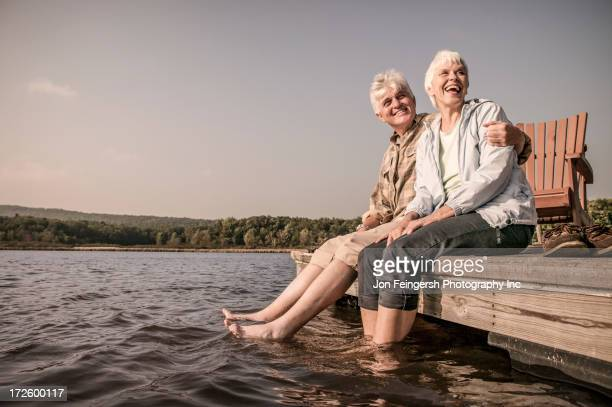 older caucasian couple sitting on wooden dock - old man feet stock pictures, royalty-free photos & images