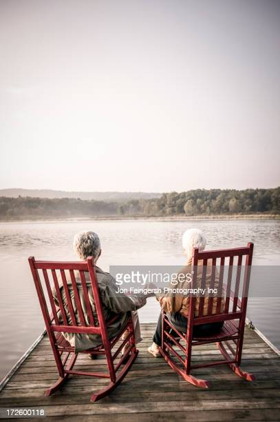 older caucasian couple sitting on wooden dock - rocking chair stock pictures, royalty-free photos & images