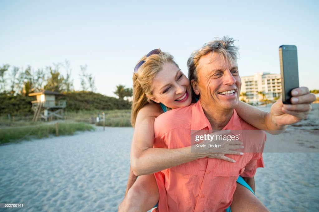 Older Caucasian couple taking cell phone selfie on beach : Foto stock
