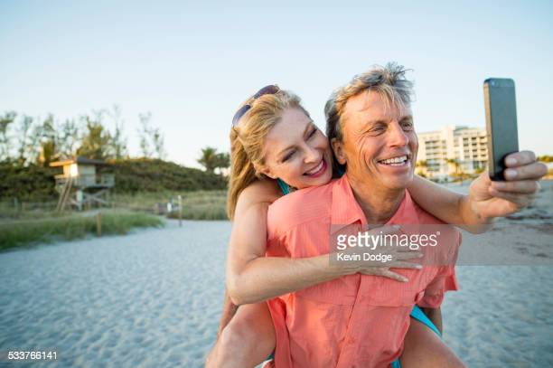 Older Caucasian couple taking cell phone selfie on beach
