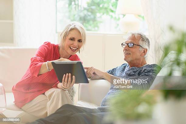 Older Caucasian couple using digital tablet in living room