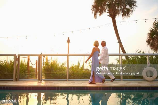 older caucasian couple walking near swimming pool - tourist resort stock pictures, royalty-free photos & images