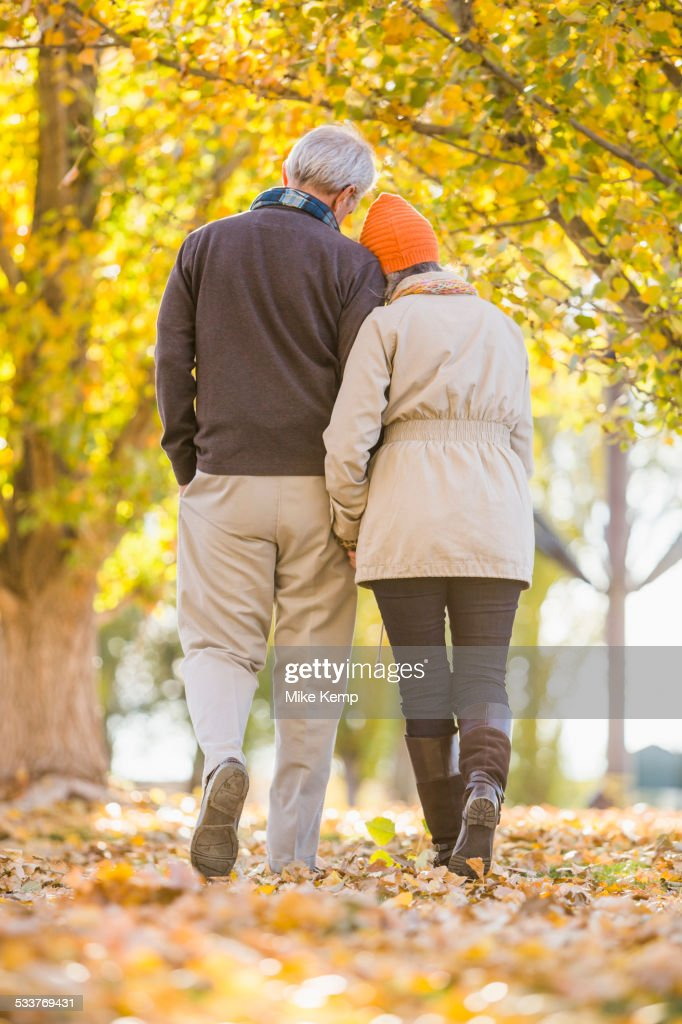 Older Caucasian couple walking under autumn trees : Foto stock