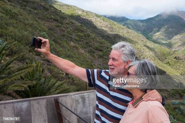 Older Caucasian couples posing for cell phone selfie