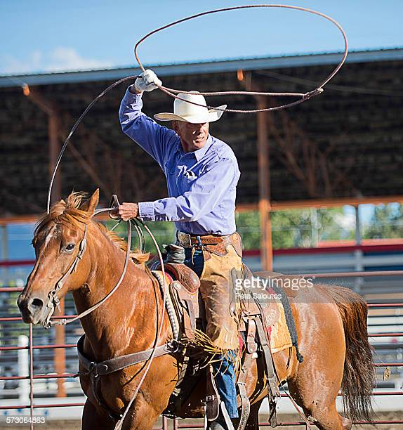 older caucasian cowboy throwing lasso at rodeo - lasso stockfoto's en -beelden