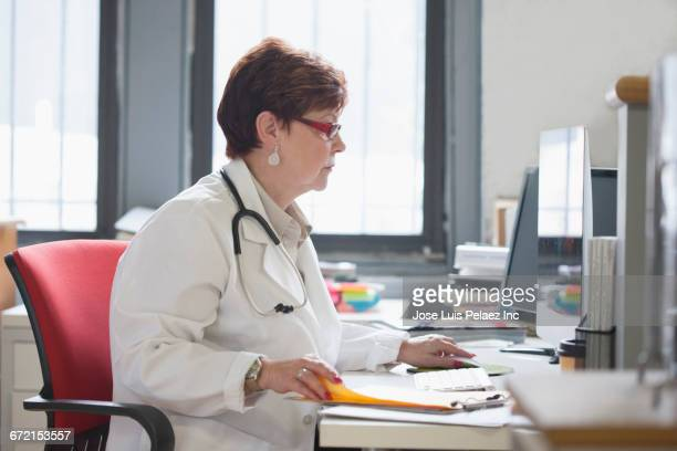 Older Caucasian doctor using computer at desk