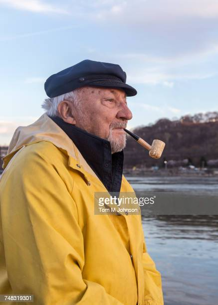 Older Caucasian fisherman near water