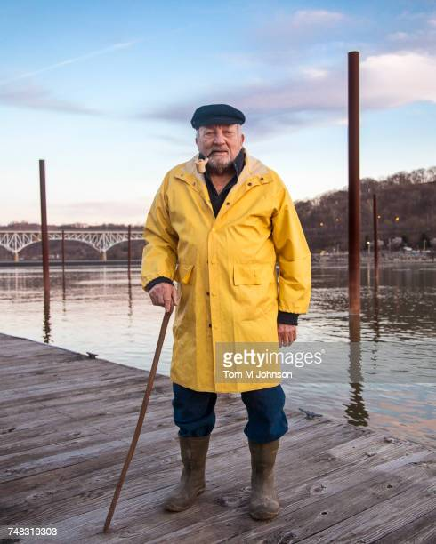 Older Caucasian fisherman standing on dock