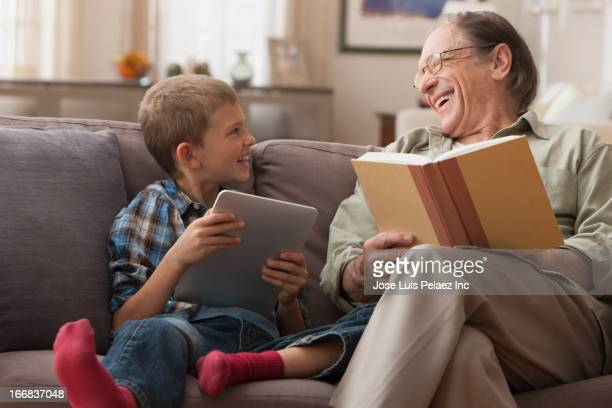 Older Caucasian man and grandson relaxing on sofa