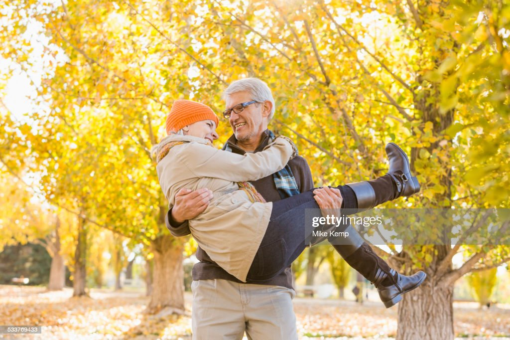 Older Caucasian man carrying wife under autumn trees : Foto stock