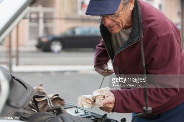 older caucasian man checking oil in car - oil change stock pictures, royalty-free photos & images