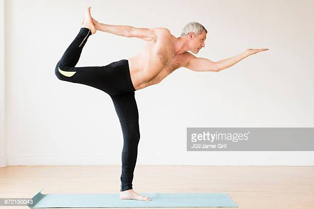 older caucasian man doing yoga on exercise mat - aging process stock photos and pictures