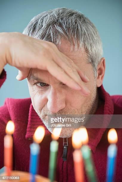 Older Caucasian man frowning at birthday cake