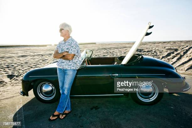 Older Caucasian man leaning on convertible car with surfboard on beach